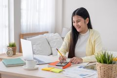 Asian female freelancer reading report on laptop and jot down note on table in bedroom at home.Work at home concept.work from home royalty free stock images