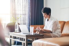 Asian female freelancer sitting on couch thinking & working on laptop at home. Asian female freelancer sitting on couch writing & working on laptop at home stock photography