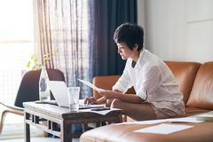 Free Asian Female Freelancer Sitting On Couch Thinking & Working On Laptop At Home Stock Photos - 148529853