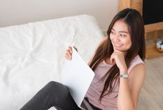 Asian female freelancer smile and holding laptop with rest leg o Stock Images