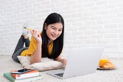 Asian female freelancer working on laptop computer at home.woman lying down on carpet at brick wall.working online lifestyle.  stock photo