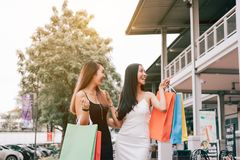 Asian female friends holding shopping bag and walking outside th. E mall Stock Photos