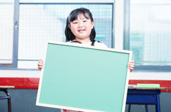 Asian female girl holding empty chalkboard in primary classroom Stock Photography