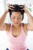 Asian female giving herself gentle head massage. Young Asian female giving herself gentle head massage Royalty Free Stock Image