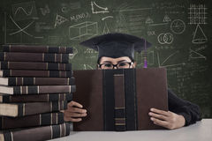 Asian female graduate peeking from behind a book Royalty Free Stock Photo