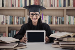 Asian female graduate show touchpad at library Royalty Free Stock Photography