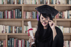 Asian female graduate smiling at library Stock Image