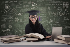 Asian female graduate typing on laptop in class Stock Image