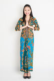 Asian female greeting. Full length Southeast Asian woman with batik dress in greeting gesture standing on plain background Stock Images