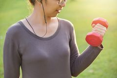 Asian female in grey sportswear is lifting dumbbell. stock images