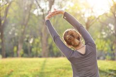 Asian female in grey sportswear workout at the park. royalty free stock photos