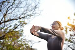 Asian female in grey sportswear workout at the park. royalty free stock images