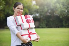 Asian female holding stack of gift boxes stock image