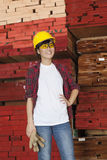 Asian female industrial worker looking away with stacked wooden planks in background Stock Photo