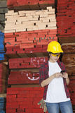 Asian female industrial worker using cell phone with stacked wooden planks in background Stock Image