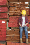 Asian female industrial worker using tablet PC while sitting on stacked wooden planks Stock Image