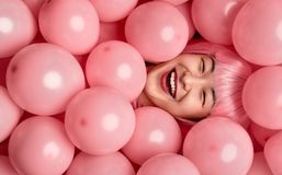 Asian female laughing under pink balloons stock photos