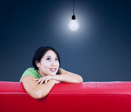 Asian female looking at lamp on red sofa. Asian female sitting on red sofa under lit bulb Stock Photography