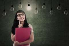Asian female looking at light bulbs in class Royalty Free Stock Photography
