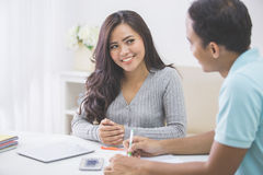 Asian female and male student studying together at home. Portrait of asian female and male student studying together at home Royalty Free Stock Photos