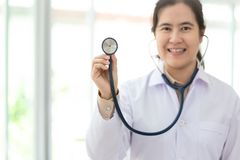 Asian female medical doctor in dressing gown holding stethoscope in the hand at hospital, physician listening through stethoscope royalty free stock photography