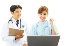 Asian female nurse and doctor. Asian female nurse using lalptop and smiling doctor Stock Photography