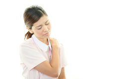 Asian female nurse. Having a shoulder pain Royalty Free Stock Photography