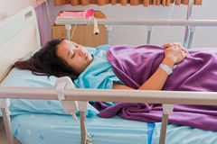 Asian female patient on bed. Asian female patient lay down on bed in hospital Stock Photos
