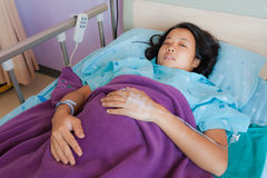 Asian female patient on bed. Asian female patient lay down on bed in hospital Royalty Free Stock Photos