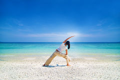 Asian female performing yoga on a beach Royalty Free Stock Images