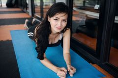 Asian female planking in fitness. Beautiful Healthy Asian woman work out or exercise by planking on yoga sheet in fitness gym floor of sport club. Portrait of Royalty Free Stock Photography