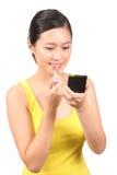 Asian female putting on lipstick Royalty Free Stock Image