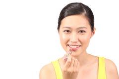 Asian female putting on lipstick - Series 2 Royalty Free Stock Photo