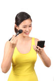 Asian female putting on makeup Royalty Free Stock Image