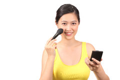 Asian female putting on makeup Royalty Free Stock Photography