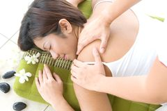 Asian female receiving back massage in spa Royalty Free Stock Photo