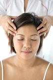 Asian female receiving gentle head massage stock images