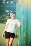Asian female relax and smile standing on tennis court Royalty Free Stock Photography