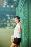 Asian female relax and smile standing on tennis court Stock Image