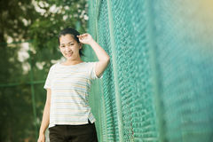 Asian female relax and smile standing on tennis court Royalty Free Stock Image