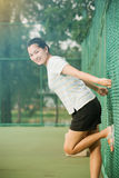Asian female relax and smile standing on tennis court Royalty Free Stock Images