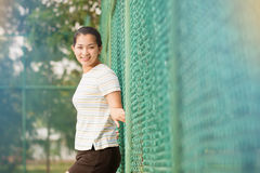 Asian female relax and smile standing on tennis court Royalty Free Stock Photos