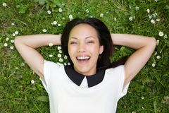 Asian female relaxing on grass and smiling Royalty Free Stock Photo