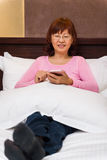 Asian female relaxing with phone Royalty Free Stock Photography