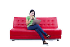 Asian female relaxing on red sofa - isolated Stock Photo