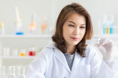 Asian female scientist poses in laboratory stock photography