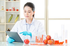 Asian female scientist research for genetic modification food. By digital tablet Stock Photo