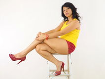 Asian female sitting on the top of a ladder Royalty Free Stock Images