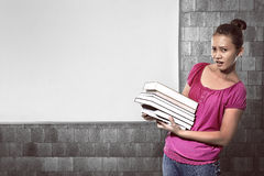 Asian female student carry a lot of books Stock Photo