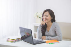 Asian female student at home studying using laptop Stock Photos